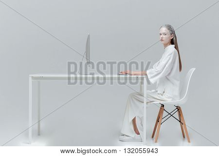 Fashion beautiful girl sitting at the desk with computer, pc over gray background