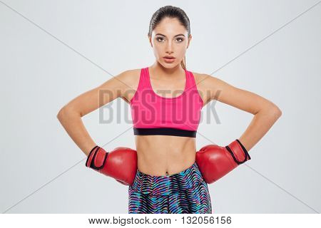 Serious sports woman in boxing gloves looking at camera isolated on a white background
