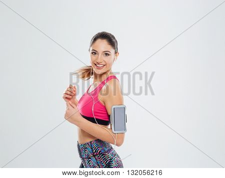 Smiling sports woman listening music in earphones isolated on a white background and looking at camera