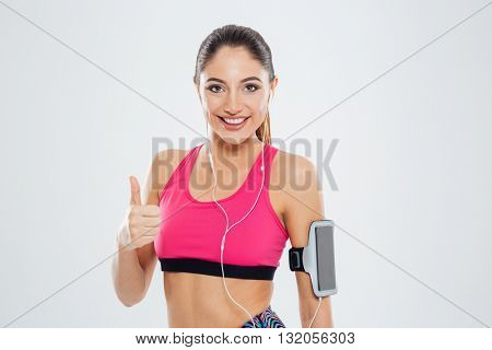 Smiling fitness woman with earphones showing thumb up isolated on a white background