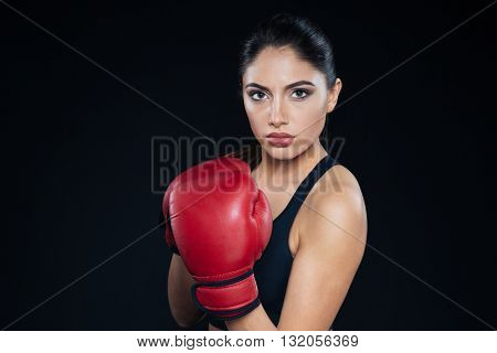 Serious fitness woman in booxing gloves looking at camera on black background