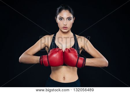 Young fitness girl with bloxing gloves looking at camera over black background