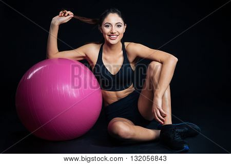 Happy cute young fitness woman sitting with purple fitball over black background