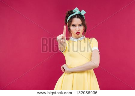 Serious strict young woman in yellow dress showing warning sign over pink background