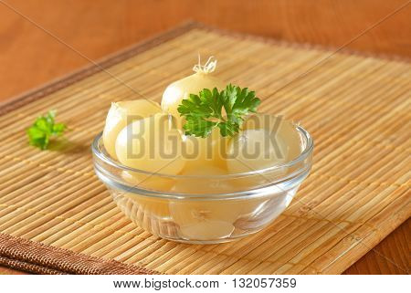 bowl of small pickled onions with parsley on bamboo place mat - close up