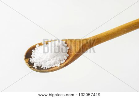 wooden spoon of coarse grained salt on white background