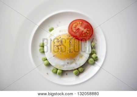 Seasoned egg with tomato, peas and sea salt served on a plate. This recipe is delicious to taste and can be done in a couple of minutes. The nutrients value are awesome and super-rich.