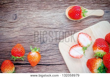 fresh strawberries on old wooden background .