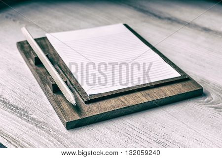 paper notes with pencil on wooden table. Vintage style.