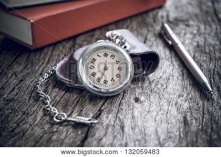 Pocket watch and book with pen On old textured wood. Vintage style.