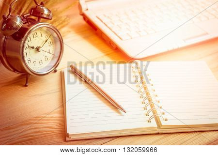 Open notebook and alarm clock on wooden background.