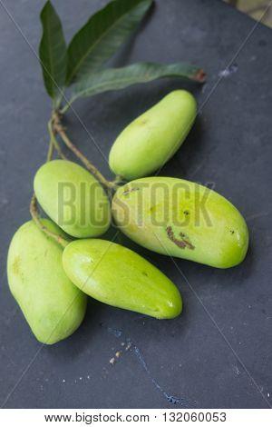 green fresh five mango on black table