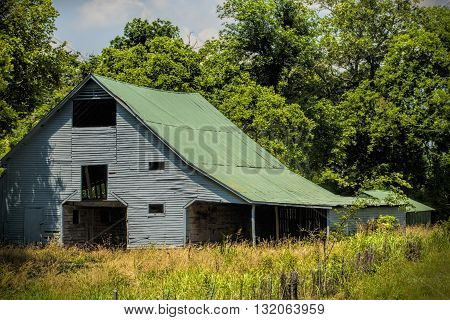 Old Gray Traditional Barn with Green Roof