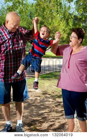 A grandpa and grandma lift their grandson into the air. Grandma is looking at her grandchild with a face as if she is making sound effects.