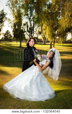 A newly married couple has a little fun dancing around after their wedding. The groom is dipping his bride and they smile at the camera. Beautiful afternoon light on a golf course.