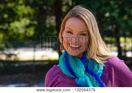 Happy blonde model in park with blue scarf
