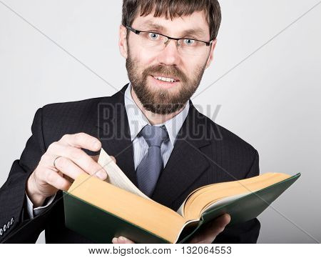 bearded businessman in a business suit and tie, reading a thick book.