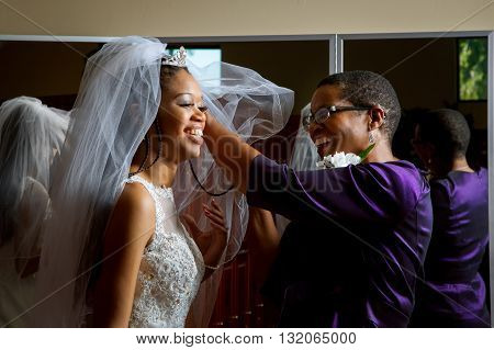 Mother of the bride adjusts her daughter's veil on her wedding day. Beautiful African American women smiling while getting the daughter ready for her wedding.