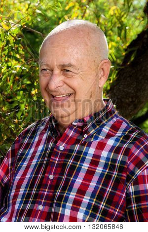 A senior man laughs on a sunny day in a park in front of trees. He is dressed in red plaid and looks ready for a picnic