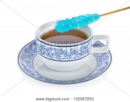 a cup of tea with blue sugar stick on a white background