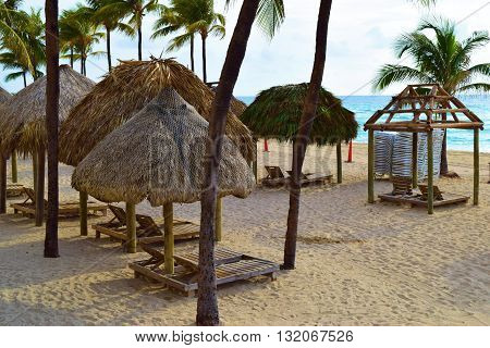 Outdoor furniture on the sandy beach including wooden lounge chairs and gazebos surrounded by Palm Trees
