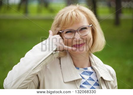 Happy smiling old blonde woman with call me gesture, against green summer park