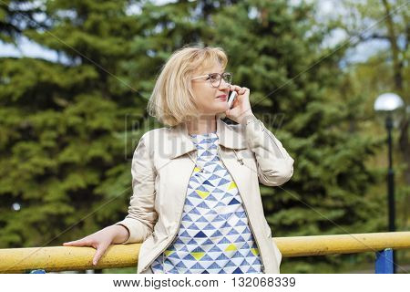 Mature beautiful blonde woman is calling on a cell phone, outdoors in spring park