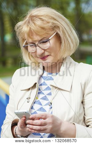 Mature beautiful woman reads the message on the phone on the spring street