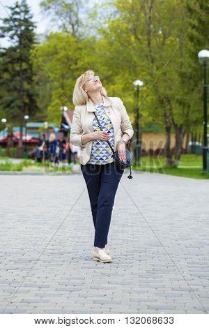 Elderly blonde woman walking in spring park