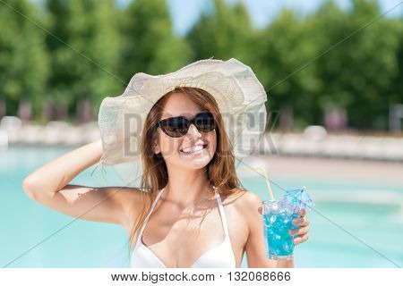 Smiling woman holding a cocktail near the pool
