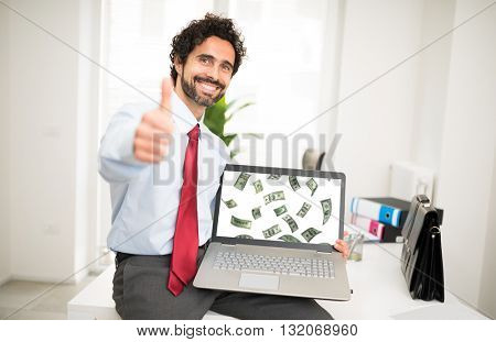 Businessman showing a laptop with a rain of money in it
