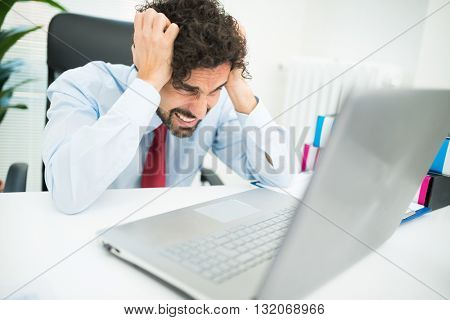 Angry businessman looking at his computer