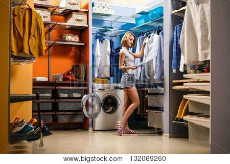 Beautiful girl is smiling and choosing clothes husband in a dressing room