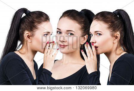 Three smiling girls whispering gossip isolated on white