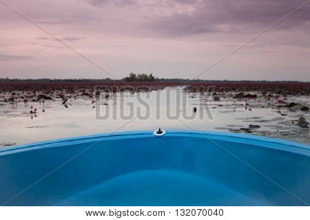 Small boat in the lake of red lotus, stock photo