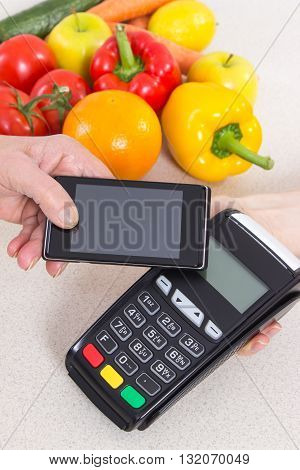 Hand of elderly senior woman using payment terminal with mobile phone with NFC technology cashless paying for shopping fruits and vegetables