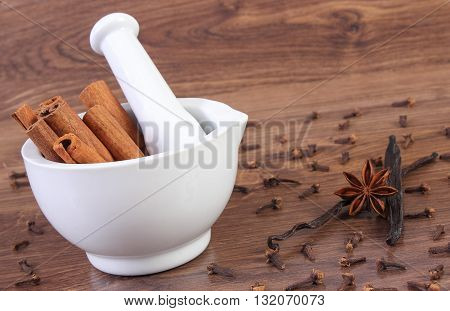 Fresh fragrant cinnamon sticks in white glass mortar and spices on rustic wooden board