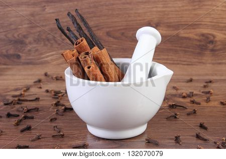 Fresh fragrant cinnamon and vanilla sticks in white glass mortar and cloves on rustic wooden board