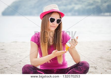 Happy smiling girl wearing straw hat and sunglasses in shape of heart on seaside and using sun lotion sun protection on beach