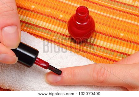 Woman applying red nail polish manicured nails of woman on soft towel nail care