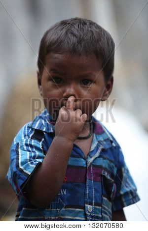 A poor little boy in blue shirt from India picking his nose.