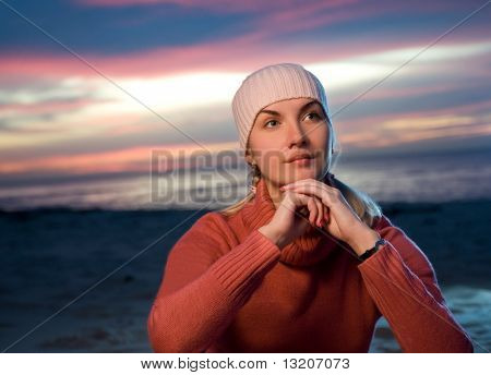 Beautiful young woman relaxing on a beach at evening