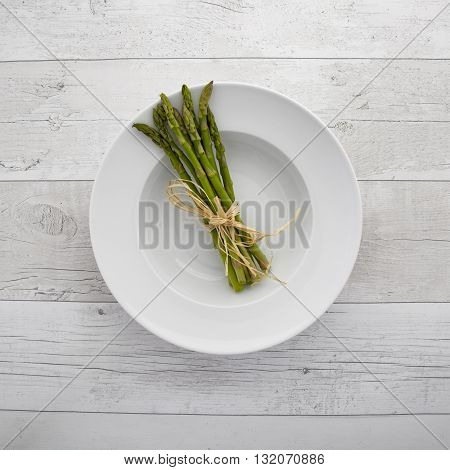 Overhead view of freash green asparagus on a white plate over a retro wooden background