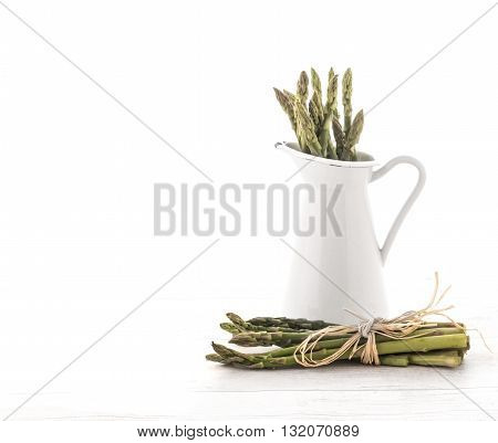 Fresh green asparagus in Jug on old wooden background