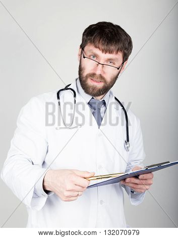 close-up portret of a Doctor holding a map-case for note, stethoscope around his neck. He stares at the camera.