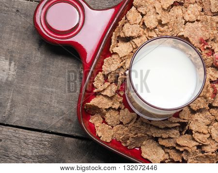 Muesli and a glass of milk on a red plate