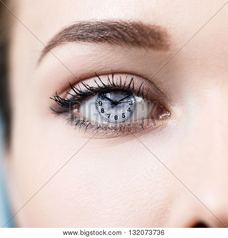 Open female gray eye with makeup and clock face inside