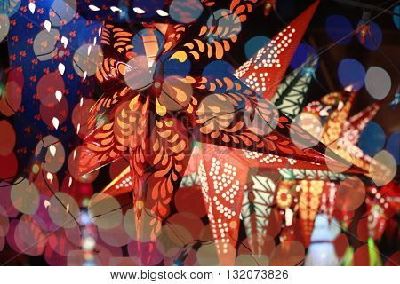 Start shaped lantern line through the colorful blur decoration lights during an Indian festival