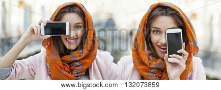 Phone display. Close up portrait of a muslim young woman wearing a head scarf, indoor