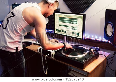 DJ creates composition in sound recording studio.  DJ playing music in sound recording studio interior. Studio recording of new club music track.